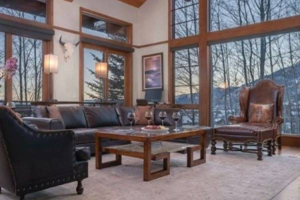 Beautiful mountain home living room, large window looking out onto winter mountain scene.