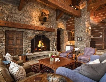 Mountain home living room with large stone fireplace and buffalo head.